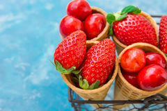 Ripe organic strawberries, glossy sweet cherries in waffle ice cream cones in wire basket, light blue background Royalty Free Stock Photos