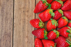 Ripe organic strawberries scattered on plank wood background, healthy food, cleansing, diet, top view. Copyspace Royalty Free Stock Photos