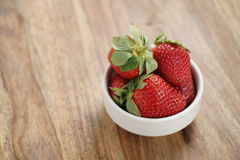 Ripe organic strawberries in white bowl on wood table. With copy space Stock Photo