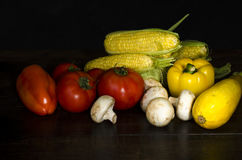 Ripe organic vegetables on wooden table at dark background Royalty Free Stock Images