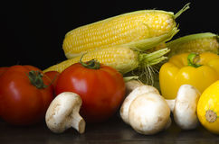 Ripe organic vegetables on wooden table at dark background Stock Images