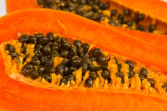 Ripe papaya. Cut in half on a white background royalty free stock image