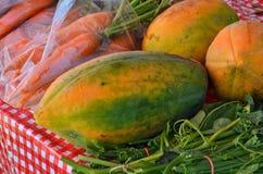 Ripe papaya fruits for sale. Ripe papaya fruits and carrots on the table Stock Photography