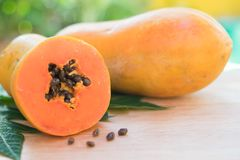 Ripe papaya with green leaf on wooden background royalty free stock photo