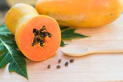 Ripe papaya with green leaf on wooden background royalty free stock images