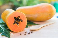 Ripe papaya with green leaf on wooden background stock photos