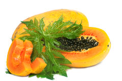 Ripe papaya and slices with seeds and green leaf Royalty Free Stock Photography
