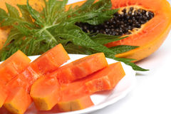 Ripe papaya and slices with seeds and green leaf Stock Photo