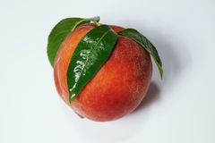 Ripe peach fruit with green leafs isolated royalty free stock image