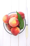 Ripe peach fruit with leaves in a white metal plate Stock Images