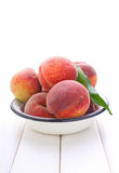 Ripe peach fruit with leaves in a white metal plate Stock Photography