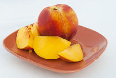 Ripe Peach fruit and slices. On a the plate isolated on white background Royalty Free Stock Images