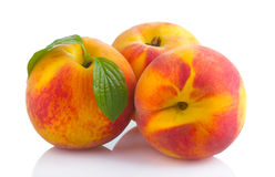 Ripe peach fruits with green leave isolated Stock Images