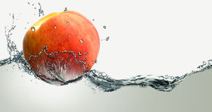 Ripe peach and splashes of water. Stock Photos