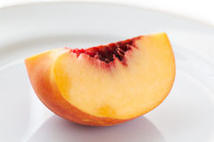 Ripe peach on the white plate, selective focus. Royalty Free Stock Photos