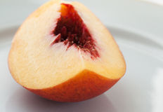 Ripe peach on the white plate, selective focus. Macro. Royalty Free Stock Photos