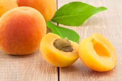 Ripe peaches and leaves on table Stock Photography