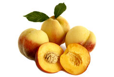 Ripe peaches with leaves on a white background. Royalty Free Stock Photos