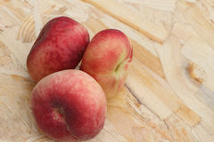 The ripe peaches lying on a wooden basis Stock Photos