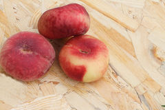 The ripe peaches lying on a wooden basis Stock Photo