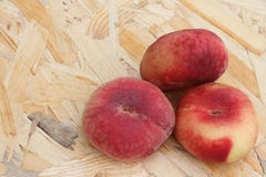 The ripe peaches lying on a wooden basis Stock Image