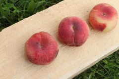 The ripe peaches lying on a wooden basis Stock Photography