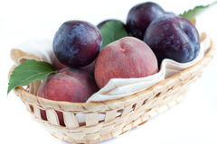 Ripe peaches and plums in the basket Royalty Free Stock Photos