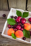 Ripe peaches, plums and cherries in a white tray stock images