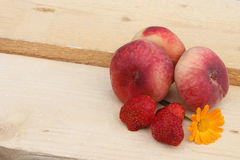 The ripe peaches and strawberry lying on a wooden basis Royalty Free Stock Photography