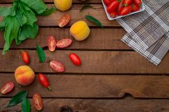 Ripe peaches and tomatoes on wooden background. Top view Royalty Free Stock Photos