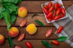 Ripe peaches and tomatoes on wooden background. Top view Royalty Free Stock Photo