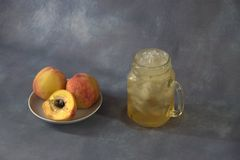 Ripe peaches, whole and half on a ceramic round plate and a glass mug with juice and ice on a gray abstract background. Close-up stock photo