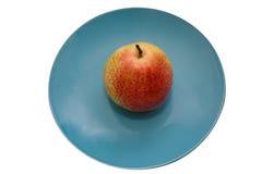 Ripe pear on a blue ceramic plate. Isolate ripe pear on a blue ceramic plate Stock Image