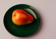 Ripe pear. On a green plate Stock Photo
