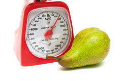 Ripe pear and kitchen scales close up on a white background Stock Photography