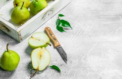 Ripe pear in the tray with a knife. On white rustic background stock photography