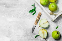 Ripe pear in the tray with a knife. On white rustic background stock image
