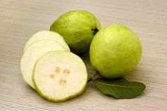 Ripe pearl guava fruits with sliced cross section on a natural wood background. Three large pearl guavas from Kaohsiung, Taiwan with one sliced into wedges to Royalty Free Stock Photos