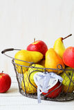 Ripe pears and apples in a metal basket Royalty Free Stock Photo
