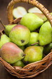 Ripe pears in a basket on  wooden background. Top view. Close-up Royalty Free Stock Photography