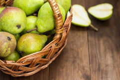 Ripe pears in a basket on  wooden background. Top view. Close-up Stock Photo
