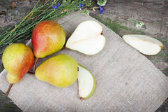 Ripe pears on canvas with flowers Stock Photo