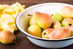 Ripe pears in an enamel plate. On a wooden table Royalty Free Stock Photography