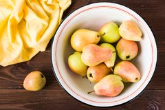 Ripe pears in an enamel plate on a wooden table. Top view Stock Images