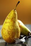 Ripe pears, fork and knife. Royalty Free Stock Images