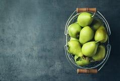 Ripe pears in metal basket on background. Ripe pears in metal basket on grey background Stock Photo
