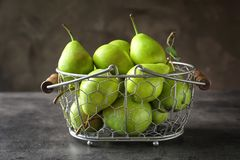 Ripe pears in metal basket on  background. Ripe pears in metal basket on grey background Royalty Free Stock Image
