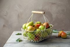 Ripe pears in metal basket. On wooden table Royalty Free Stock Photo