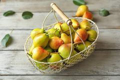 Ripe pears in metal basket. On wooden table Royalty Free Stock Photos
