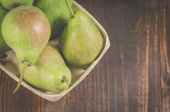 Ripe pears in a wattled box on a dark wooden background/fresh pears in a wooden box, top view and copy space stock photos